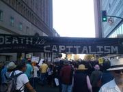 """An Oakland protest banner proclaims, """"Death to Capitalism."""""""