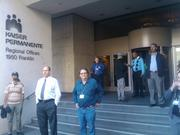 Observers watch protesters in front of Kaiser Permanente offices in downtown Oakland on Wednesday.