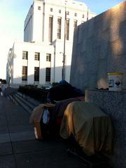 Homeless people park overloaded carts of possessions beside the Alameda County Administration Building at Oak and 13th streets in Oakland.