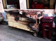 A burned dumpster where protesters lit a bonfire Wednesday night.
