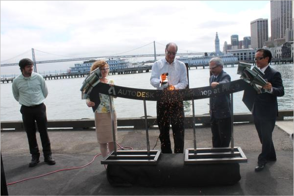 "Autodesk CEO Carl Bass grinds a steel ""ribbon"" at the company's new Pier