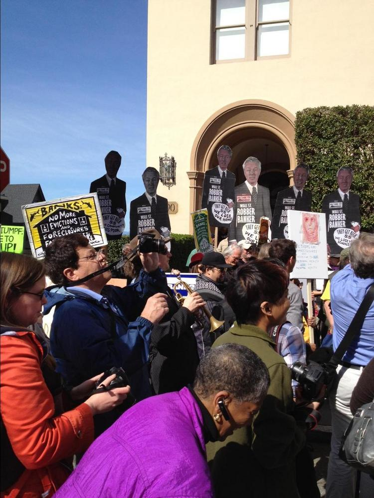 Occupy protestors gathered Saturday in front of the home of Wells Fargo Chairman and CEO John Stumpf in San Francisco's Russian Hill to deliver their own version of a foreclosure notice. Stumpf didn't make an appearance, unless you count the many placards featuring his face.