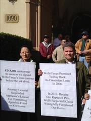 Donna and Nuno Vieira, who were among the foreclosure protestors at Wells Fargo CEO John Stumpf's home Saturday, each carried a placard discussing an element of their story about losing a second home in Reno, Nev., through a Wells Fargo foreclosure.