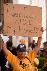 "Tanya Dennis, from Oakland, holds up a sign in front of the Wells Fargo headquarters in San Francisco on the day of the bank's annual meeting, held in Salt Lake City. ""I have been fighting Wells Fargo for four years,"" Dennis said."
