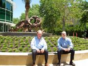 """Rich Robbins, left, and artist Fred Gelb, right, sit in front of Gelb's sculpture """"All Together Now."""""""