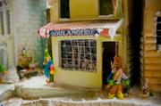 What French village is complete without a boulangerie? A marzipan elf stands guard outside the boulange door; the bakery is stocked with bread and candy glass fills the window. The boulangerie alone took six hours to build.