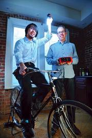 Charged up: Fenix CEO Mike Lin pedals for power, as VP Luke Filose holds the company's ReadySet storage device.