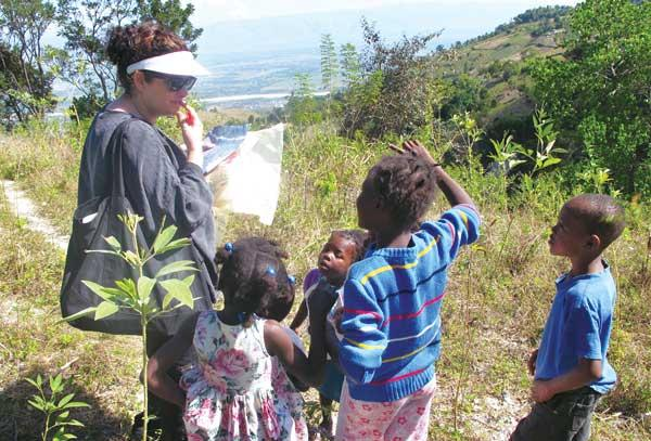 Architect Lisa Victor views the site of a school site with children in Haiti.