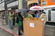 AT&T's Marc Blakeman (with red and white umbrella) talks boxes in S.F.'s Inner Sunset district.