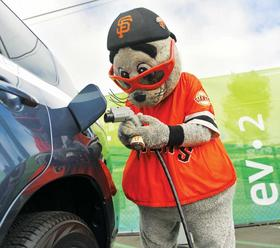 San Francisco Giants mascot Lou Seal prepares to plug in an electric car in  the parking area next to AT&T Park.