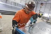 A worker from United Mechanical finishes some sheet metal duct work for the new arena.