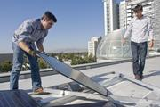 From left, Steve Frehn, engineering manager at Armageddon Energy, and Dimitry Dimov, CTO, install the company's SolarClover product on the rooftop of city hall.