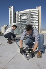 From left, Dimitry Dimov, CTO, and Steve Frehn, the engineering manager at Armageddon Energy fit together a SolarClover on the rooftop of San Jose City Hall for a demonstration installation.