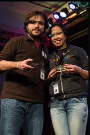 A pair of developers at the Google Glass Foundry event show off the Pioneer swag they were allowed to leave with.