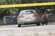 Investigators inspect the scene of the crime where the suspect's car was left on Wednesday morning in Sunnyvale.