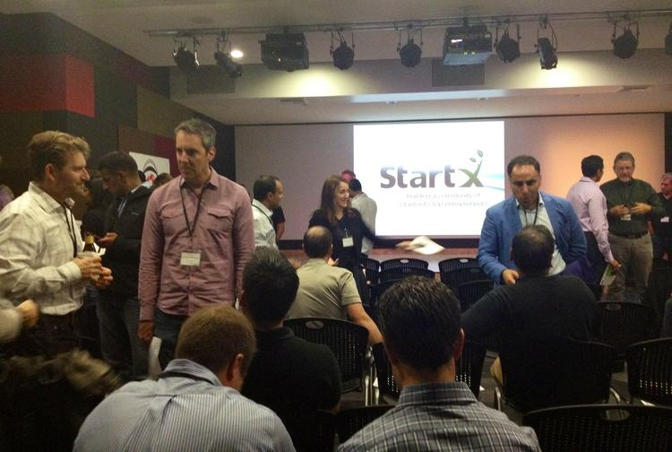 Attendees mingle before StartX's latest batch of companies pitched at a demo day event Thursday.