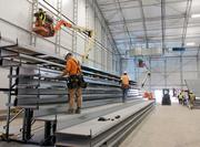 Workers from Gym Tek Inc. install bleachers behind one of the baskets at the new arena.