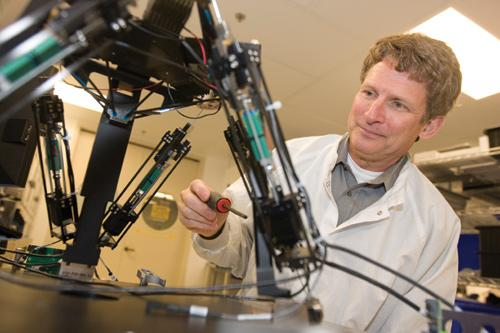 Pacific Biosciences CEO Hugh Martin demonstrates the hexapod robot on the company's DNA sequencing instrument, which produces testing results in minutes instead of days.