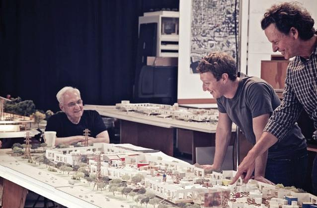 Architect Frank Gehry, left, with Facebook CEO Mark Zuckerberg, center, examine the model of the new Facebook campus that Gehry is designing.