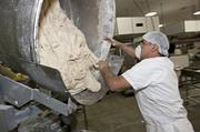 A baker kneads dough at the bakery's Sunnyvale location, the only site that makes bread for the company's wholesale customers.