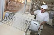A baker flours pastry dough as it is rolled out to be made into an almond pastry. Le Boulanger used 35 tons of flower a week in its bakeries.