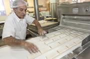 Almond pastries are ready for baking after they are folded in a machine.