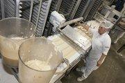 A baker loads almond filling onto pastry shells.