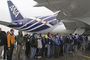 Guests try to stay out of the rain dry by standing under the wing of a 787 outside the Boeing Everett plant during the delivery ceremony to celebrate the delivery of the first Dreamliner to launch customer ANA.  Pictured is 787 number 24 off the line.