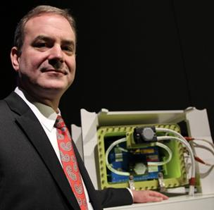Mike Sinnett, vice president at Boeing Commercial Airplanes and chief project engineer of the 787 program, with a photograph with a model of the newly redesigned battery for Boeing's 787 during a news conference in Tokyo on Friday.