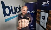 """Buck CEO Andy Kleitsch (on his own idea) drew """"BUCK"""" with a permanent marker on his fist for a photo shoot in his company's offices in Seattle."""