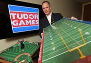 """Tudor Games President Doug Strohm stands next to the baseball game """"Ballpark Classics,"""" which he created in the 1970s. He holds another classic tabletop game, """"Football Challenge,"""" in the Seattle offices of Garrigan Lyman Group."""