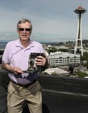 """Retired Seattle Times photographer Bruce McKim is pictured holding a vintage Speed Graphic 4x5"""" film news camera from the same Seattle rooftop spot where he shot a nighttime view of the 1962 Seattle World's Fair as part of Sylvania's """"Big Shot"""" annual photo project. More images and story here."""