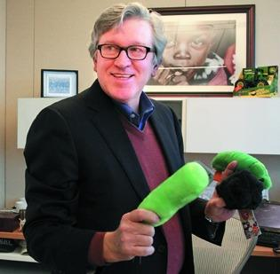 Jeff Raikes in his office at the Bill & Melinda Gates Foundation. In this December 2011 photo, Raikes holds stuffed toys modeled after diseases and infections.