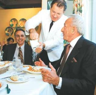 Michael R. Mastro, right, dines with  son Michael K. Mastro at their usual table at Seattle's Il Terrazzo  Carmine restaurant in 2005. Waiter Walter Vianello shares in the banter. The younger Mastro is traveling to France to be with his father and stepmother at a court hearing Wednesday.