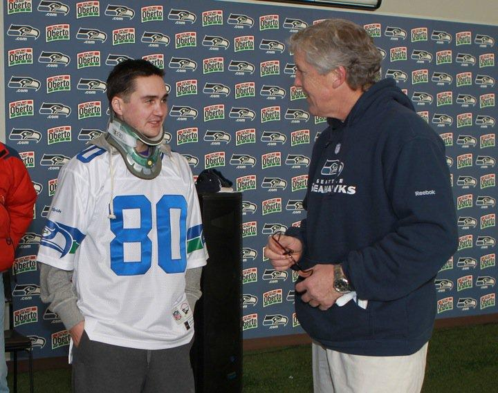 Army 1st. Lt. Justin Baumann, at Seahawk's Renton headquarters,  chats with Seattle Seahawks coach Pete Carroll before the winning game against St. Louis.