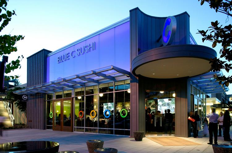 Blue C Sushi restaurants, like this one in downtown Seattle, deliver food on conveyor belts and customers take what they want as it passes by. The Seattle-based group is expanding into California.