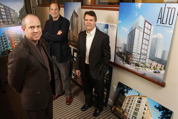 From left: Jim Atkins, managing director of Harbor Urban, Matt Burton, partner in Urban Partners and Doug Dailey, president and CEO of Harbor Properties, with artist renderings of some of their real estate projects in the Harbor Properties offices in Seattle on Thursday.