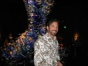 Jeweler Steven Goldfarb poses in front one one of Dale Chihuly's giant chandeliers, one of thousands of pieces of glass displayed in Chihuly Garden and Glass, opening to the public today, Monday, after a series of pre-opening parties attracted hundreds of invited business and community leaders.