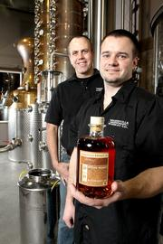 Best friends since their days at Central Washington University, Woodinville Whiskey Company co-founders Orlin Sorensen (left) and Brett Carlile (right) in their distillery with a bottle of their Microbarreled Bourbon Whiskey.