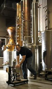 """Woodinville Whiskey Company co-founder Orlin Sorensen pushes a pump past the 265-gallon pot still with a pear-shaped whiskey helmet, 16-plate bubble-cap """"Superaromator"""" rectification column and condenser in the distillery."""