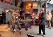 Gaffer Jimmy Mongrain spins a Persian glass piece while Dale Chihuly shapes it in the hotshop at his Boathouse.