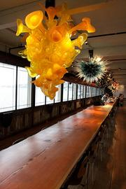 The Evelyn Room at Dale Chihuly's Boathouse features his chandeliers, an 85-foot-long table made from a single slab of Douglas fir, sweeping views of Lake Union and a number of his collections.