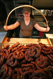 Shawnna Kenney, 39, hand-forms a pretzel at Tom Douglas' Brave Horse Tavern. The popular menu item is hand-shaped and baked daily at the Brave Horse.
