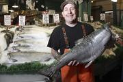 Chris Bell, of Pike Place Fish Market, holds a 25 pound king salmon caught off the Washington coast.