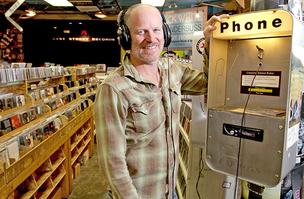 Matt Vaughan, President of Easy Street Records, at a former payphone turned listening booth at his Queen Anne location.