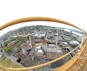 """The Bill & Melinda Gates Foundation's campus in Seattle began to take form in 2010, as seen looking north through a fish-eye lens from atop a 200-foot construction crane. At lower left, sections of """"green"""" roof cover the parking garage off Fifth Avenue. Mercer Street bisects the photo horizontally, forming the campus' northern edge. Lake Union is at upper right."""