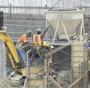 POURING IT ON: Employees of Sellen Construction Co. maneuver a concrete-pouring bucket. The Bill & Melinda Gates Foundation campus was the largest project that Sellen Construction had ever managed.