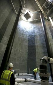Workers for Sellen Construction in the interior of the 60-foot-deep thermal energy storage tank. The 750,000 gallon underground tank stores rainwater for use in reflective pools, irrigation and toilets.