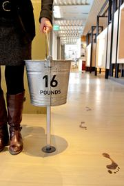 A display to illustrate that millions of people have to walk three miles every time they need to get water includes a bucket that simulates the weight of two gallons of water and a path of footprints that runs the length of the Bill & Melinda Gates Foundation visitors center. Visitors would have to walk 36.4 loops to cover the 3 miles.