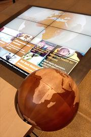 The Family Foundation gallery of the Bill & Melinda Gates Foundation visitors center includes a large screen that shows programs from around the world in which the foundation is involved. Visitors can rotate the wooden globe and it rotates the globe on the big screen.